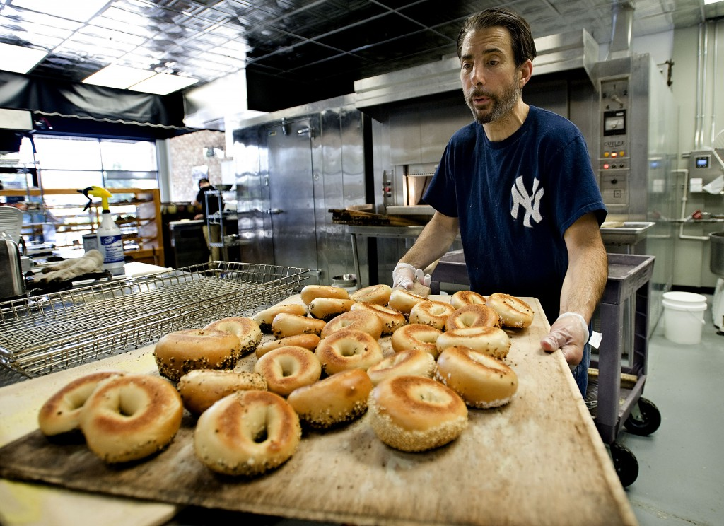 New York native Chris Sclafani takes a board full of freshly baked  bagels out of the oven inside his new bakery,  Sclafani's New York Bagels and Bread, in Kernstown Commons.  Rich Cooley/Daily