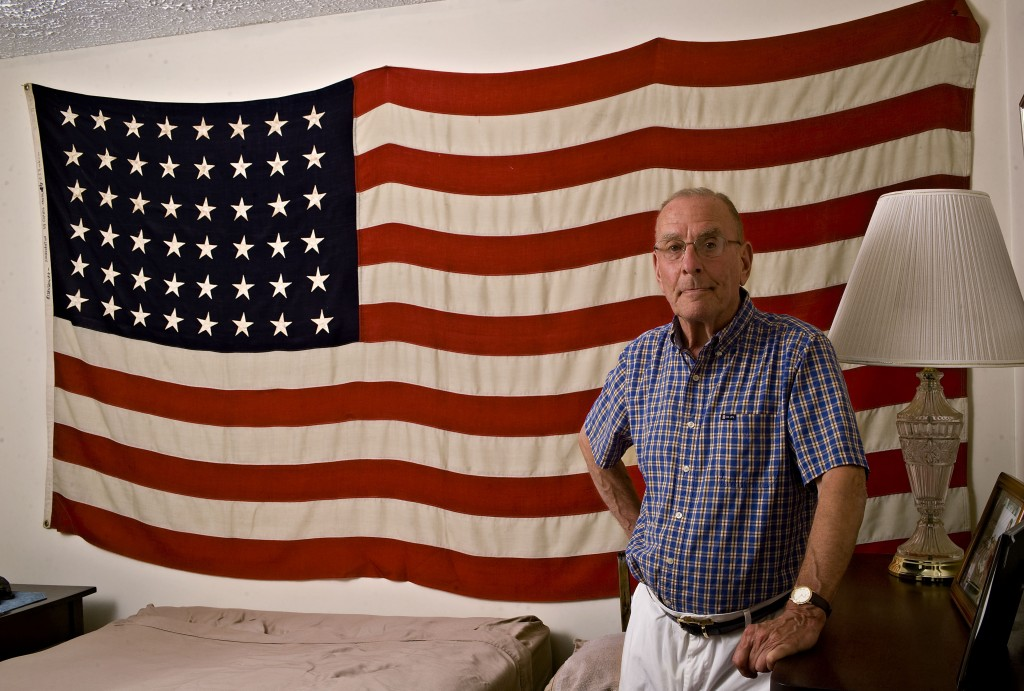 Robert C. Rinehimer, Jr., 72, of New Market, stands by the linen flag in his home that flew over the Capitol during the inauguration of President Dwight D. Eisenhower.  Rich Cooley/Daily