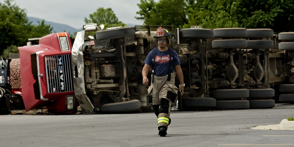 """Pete Quinones, a Stephens City Volunteer Fire Department member, walks across the parking lot outside Lord Fairfax Community College where this tractor trailer overturned on Friday morning. The tractor trailer deposited what police described as a """"significant"""" amount of mulch at the Middletown campus. No one was injured and there was no damage to property. The driver was not charged.   Rich Cooley/Daily"""