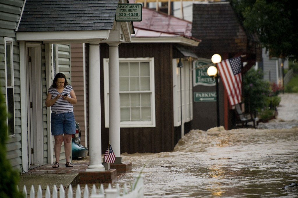 Beverly Griffin taps in a number on her phone as she stands on the front porch of her apartment on South Main Street in Woodstock on Monday morning. Floodwaters bounce off the front of the Springhouse Tavern and shut down this section of Main Street several hours.  Rich Cooley/Daily