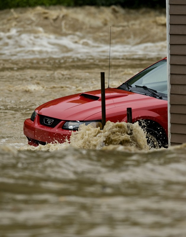 A car is surrounded by water off South Main Street between Spring and South streets as floodwaters from Spring Hollow rushed behind it during a flash flood on July 13..  Rich Cooley/Daily