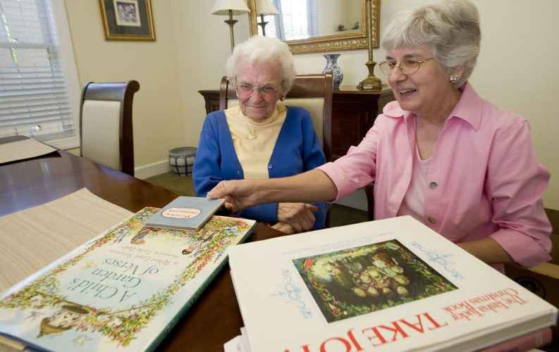 At left, Iris Vann, 97,  a former elementary school teacher in Shenandoah County, and Laura Wade, a retired Sandy Hook Elementary librarian, look over children's books by  author Tasha Tudor, who lived in Vermont and died in 2007. Wade recently visited the author's 1830s-replica home, which is now a museum, and got Tudor's son to autograph a book for Vann.  Rich Cooley/Daily