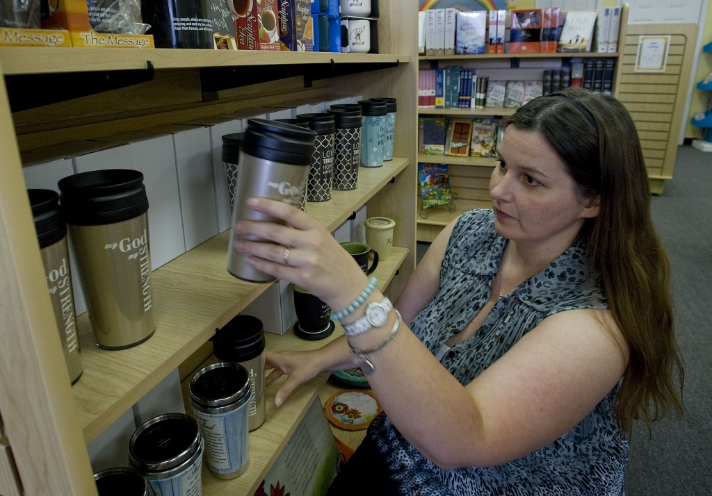 Bonnie Hart stocks mugs on the shelves of her new store, The Grace Place Shop, which is located on East Main Street in Front Royal. The Christian-based gift shop is one of several new businesses cropping up along Main Street. Rich Cooley/Daily