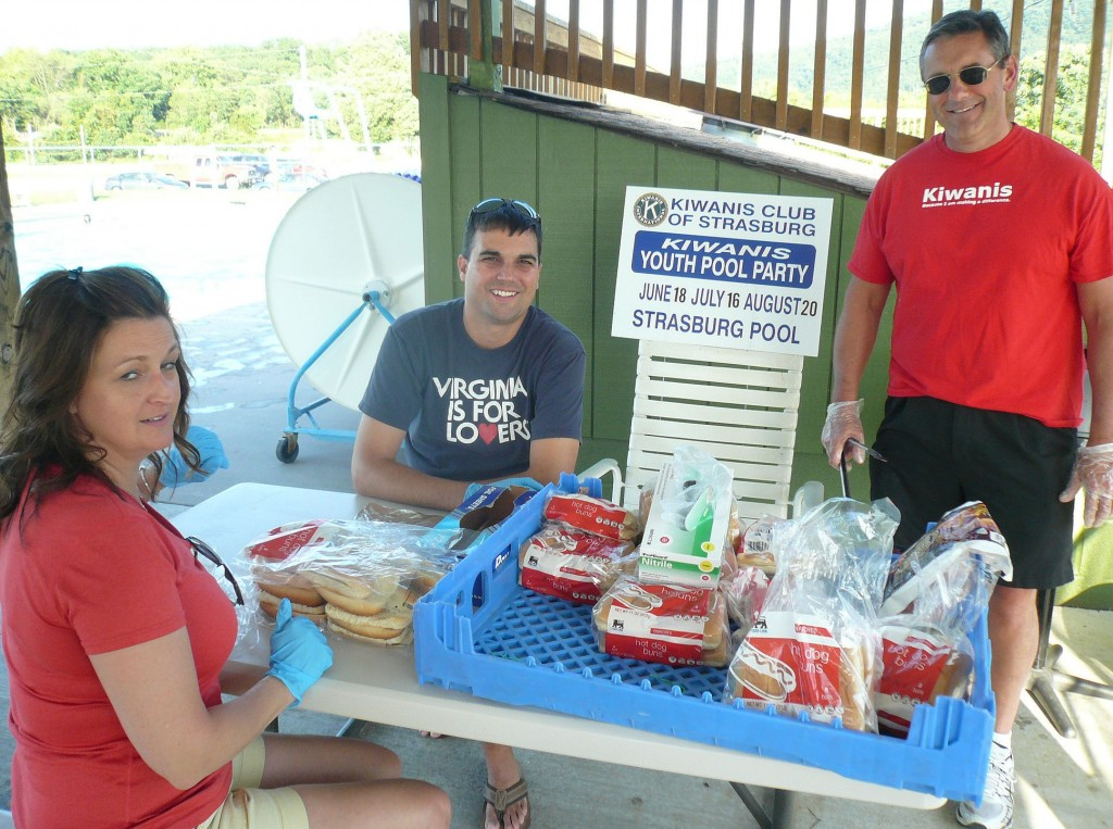 Strasburg Kiwanis Club members Amy Lineweaver, from left, Kyle Butler and club President Bruce Berger take a break  from cooking hot dogs for the swimmers at the club's free swim meet, which is held one evening each month at the Strasburg pool.  The club rents the pool and provides hot dogs to all the swimmers and their parents at each event. The next swim meet will be held Aug. 29. Information: Doug Butler,  540-771-0253.