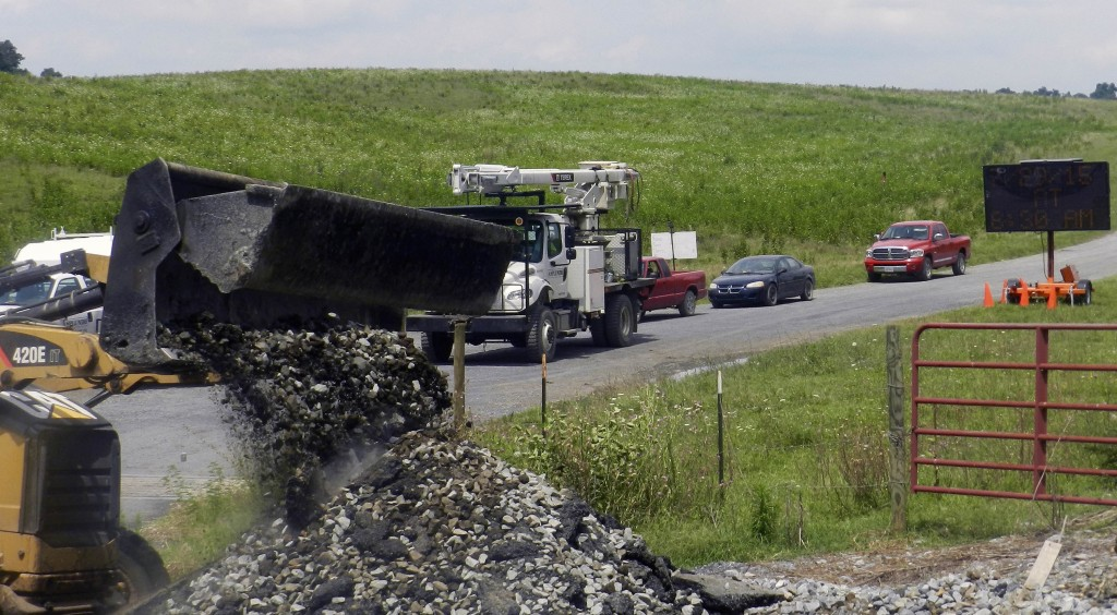 Contracted crews for Norfolk Southern use a front-end loader to removed  debris  at the railroad crossing on Shenandoah Farms Road.  The crossing was closed for several hours on Wednesday. Kevin Green/Daily