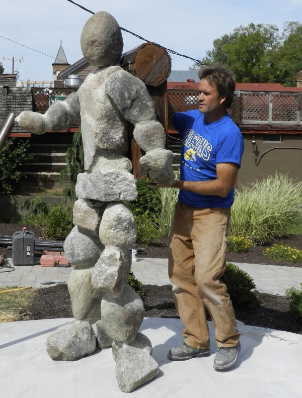 "Sculptor Craig Gray places the finishing backpack element on    his ""PAC-Man"" sculpture in  Woodstock's Jane Garden.   Rachel Mahoney/Daily"