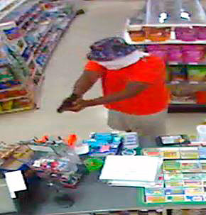 An armed robber points a gun at a clerk at the 7-11 store on Aylor Road near Stephens City early Tuesday morning. Security camera image