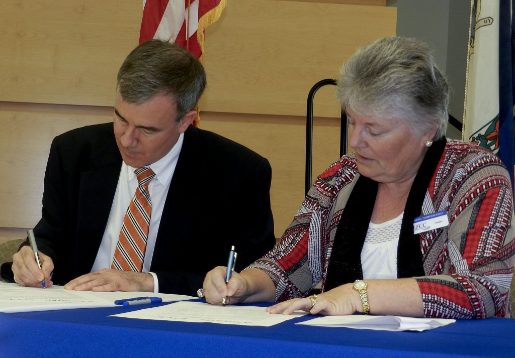 Shentel President Chris French, left, and Cheryl Thompson-Stacey, president of Lord Fairfax Community College, sign an agreement for a new partnership that promises more job opportunities for  students. Kevin Green/Daily