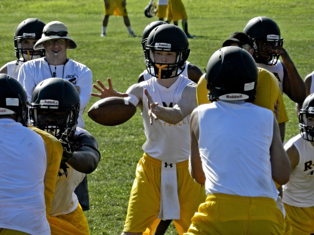 Randolph-Macon Academy  quarterback Peter Blair, center, fields a snap during a drill at a recent practice in Front Royal.    Brad Fauber/Daily