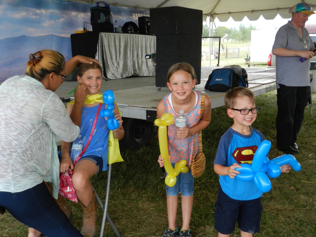 Michelle Owens, of Front Royal, paints the face of Jillian Brunton, 10, of Edinburg at the Shenandoah County Fair on Tuesday. Also pictured are 10-year-old Samantha Shenk, of Edinburg, at center, and her brother Aaron Shenk, 5. At far right, magician Kevin Owens makes balloon animals for the crowd. Kaley Toy/Daily
