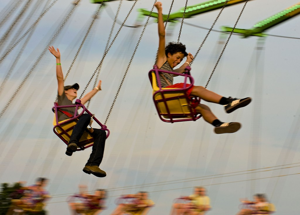Jeremy Viar, 13, left, of Woodstock, and Ty Ryman, 12, right, of Woodstock,  enjoy the breeze as they  ride the swings at the Shenandoah County Fair.  Rich Cooley/Daily