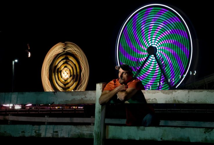 Justin Cole, 32, of Waynesboro,  watches the rides along the midway the Ferris  wheel and Zipper ride spin in the background at the Shenandoah County Fairgrounds. The fair ends today.  Rich Cooley/Daily
