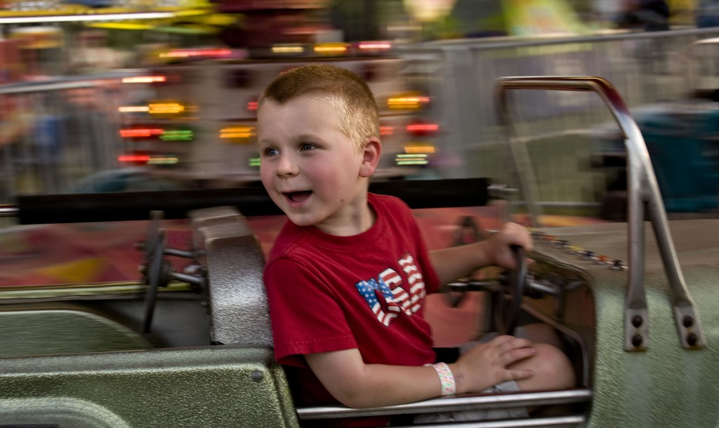 Joshua Postupak, 5, of Strasburg rides a jeep at the carnival grounds at the Shenandoah County Fair in Woodstock.   Rich Cooley/Daily
