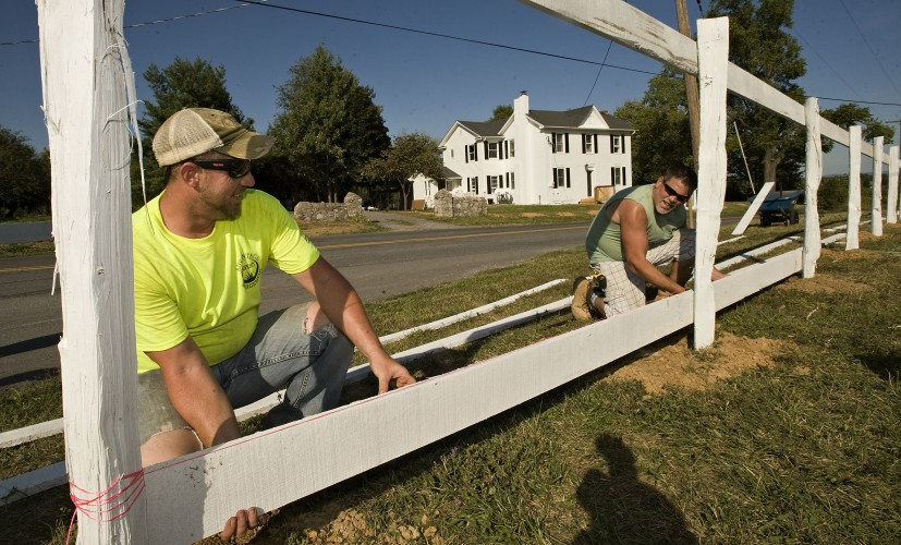 Landscape supervisor Matt Stine, left, and carpenter  J.R. Shull, right, construct this fence row outside the parking lot of the Third Winchester Battlefield Visitor Center  in Winchester on Wednesday. They are employees of Winchester firm Advantage Property Management Inc, which donated its employees for the project. Rich Cooley/Daily