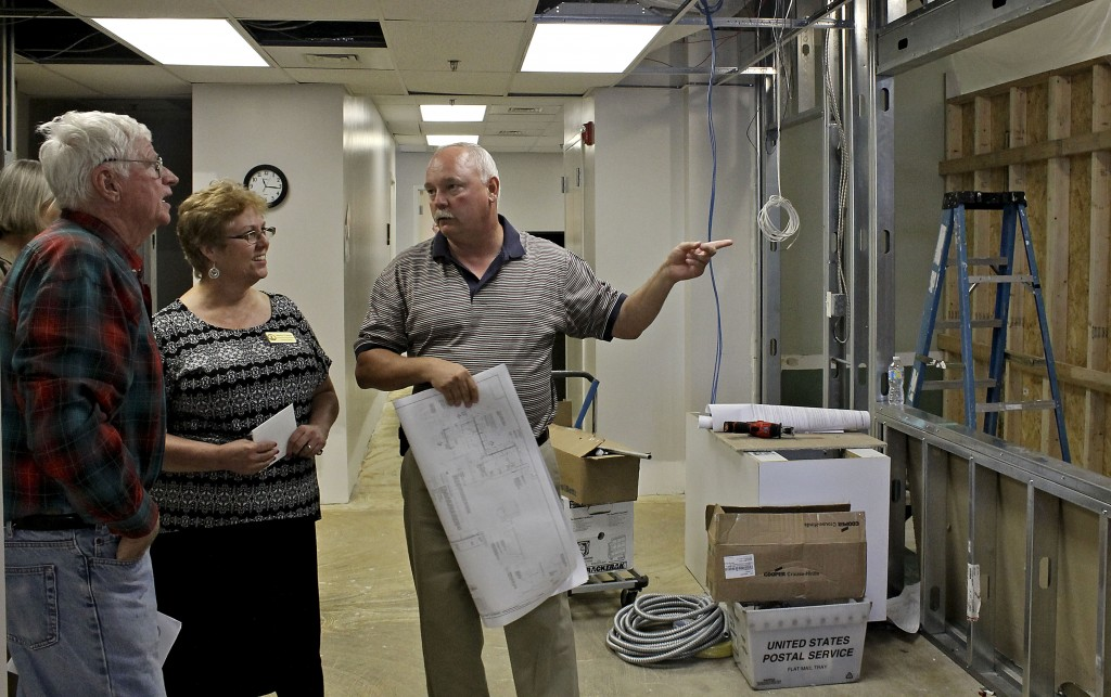 Warren County Supervisor Archie Fox, left, and Commissioner of the Revenue Sherry Sours, center, listen as Project Manager Jeff Hayes describes renovations underway in the customer service area of the commissioner's office on Wednesday.  Alex Bridges/Daily