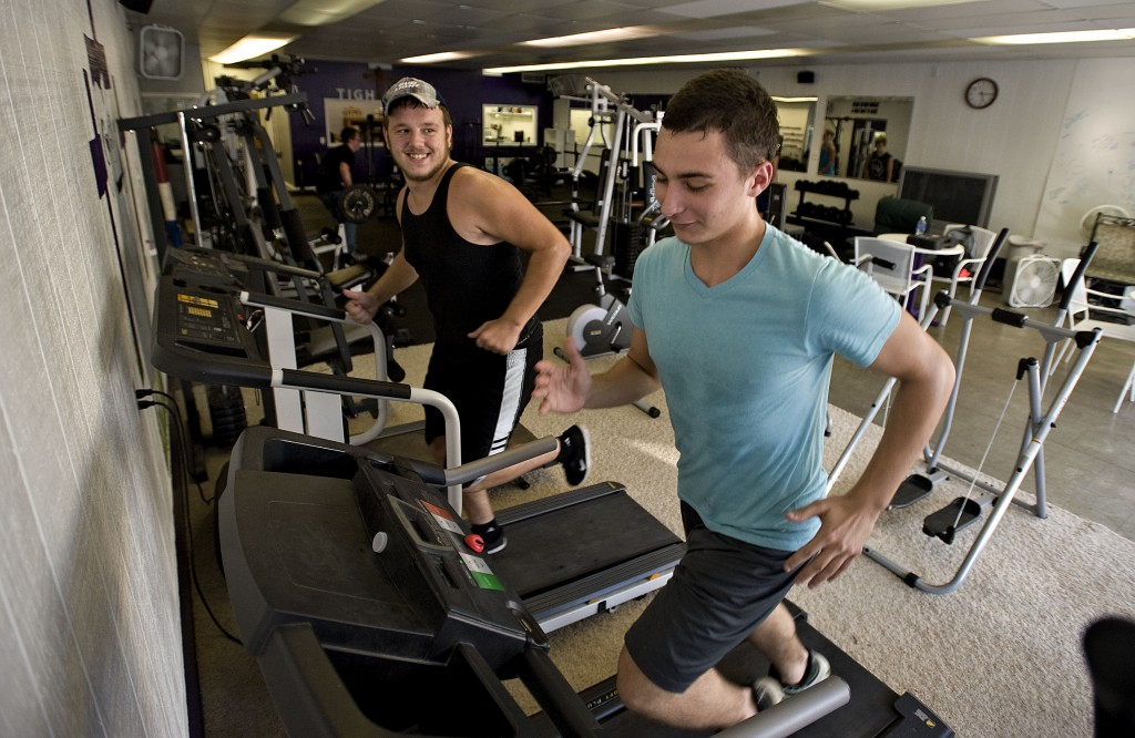 Justin Palmer, left,  and Jesse Baker, right, both 16, run on treadmills inside the Tight'n Up Gym in Strasburg.  Rich Cooley/Daily
