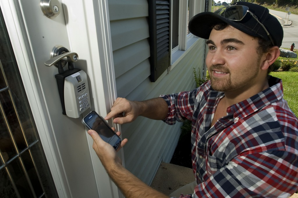 Nathan Gochenour, a real estate agent for Skyline Team Real Estate, uses a smart app on his Android phone to demonstrate how new technology is being used to access a key lockbox on a home. Rich Cooley/Daily