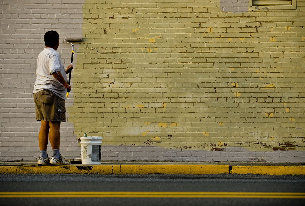 Charlie Taylor, of Stanardsville, paints the exterior wall of the Strasburg Emporium along East King Street recently. Taylor is employed by the Emporium.  Rich Cooley/Daily