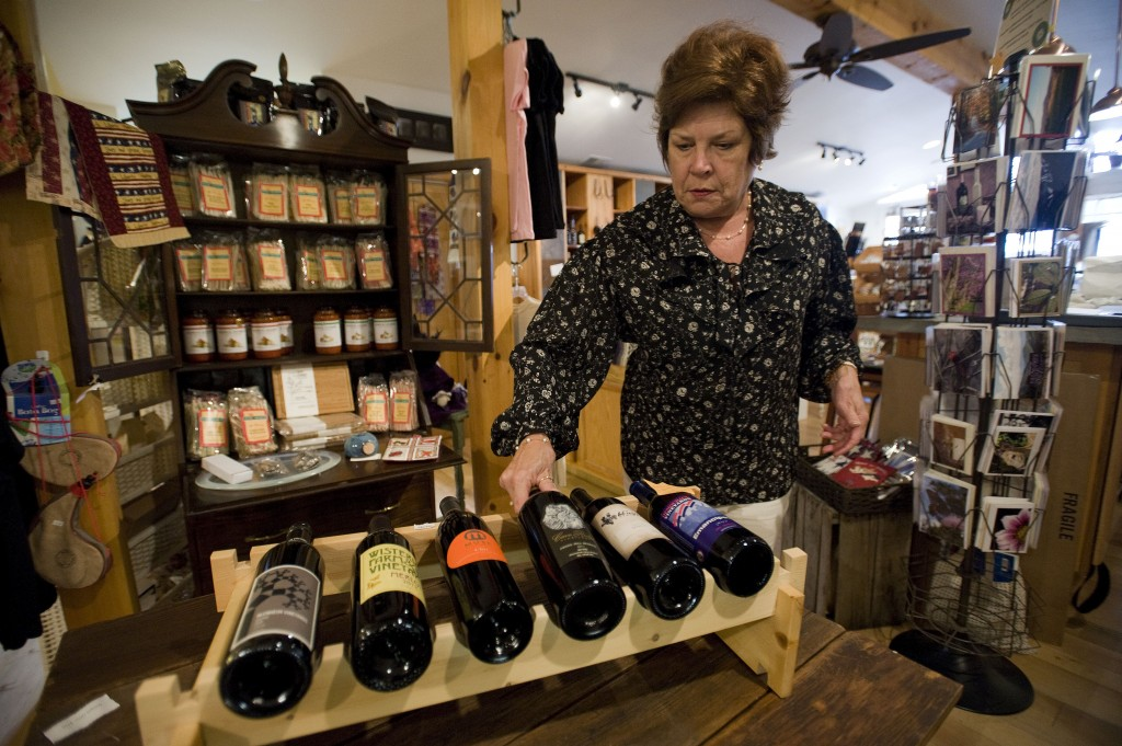 Vicki Ruckman, co-owner of All Things Virginia at the Farmhouse, loads a rack of Virginia wines at her store along Main Street in Woodstock. Wine and cider sales in Virginia had record sales this year.   Rich Cooley/Daily