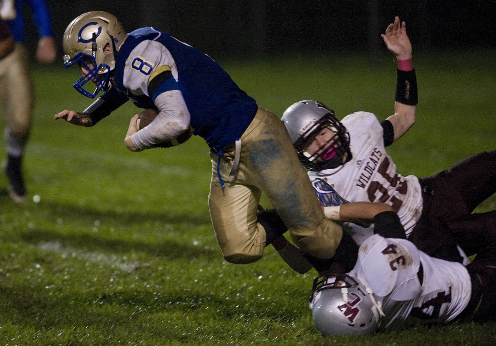 Central's Hank Hoover dives forward for yards as Warren County's Rhett Tierney and Brett Dickerson make the tackle during a game on Oct. 1 in Woodstock.    Rich Cooley/Daily file