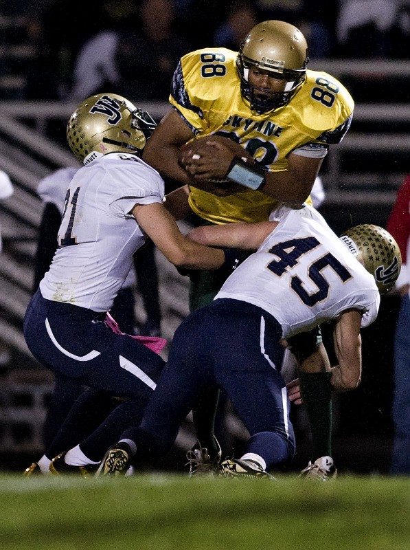 Skyline's Antwan Swain hauls in a pass while James Wood's David Funk and Ryan Funkhouser tackle him during their game on Oct. 16 in Front Royal. The Hawks host Warren County on Friday.   Rich Cooley/Daily file