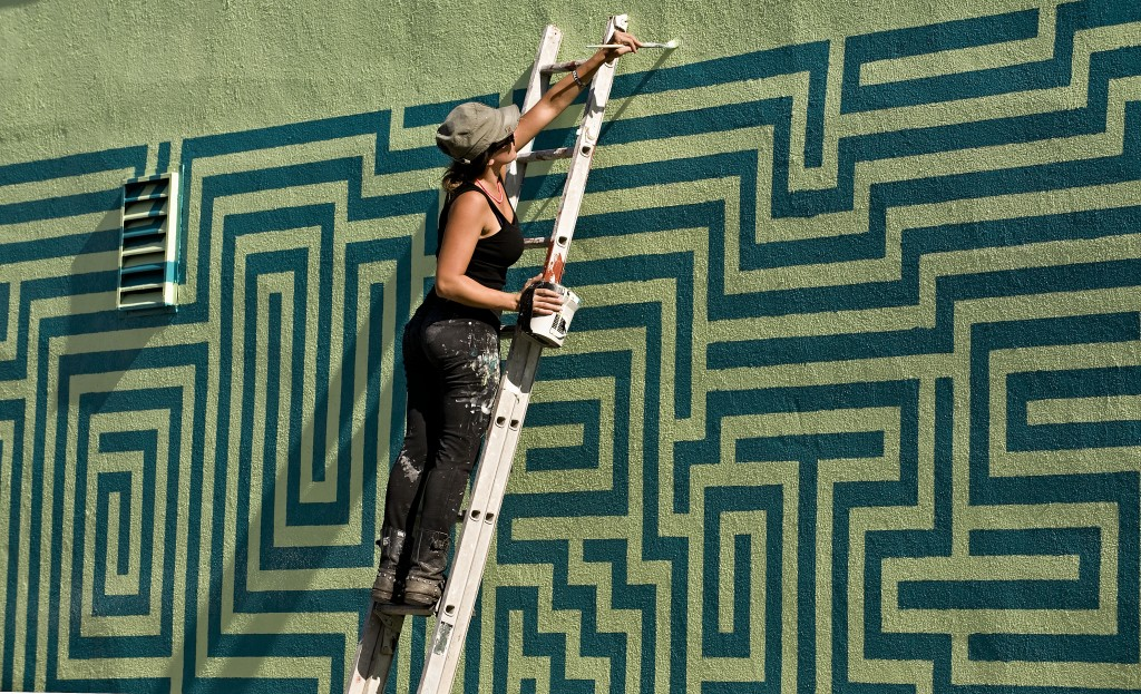 Ann Lewis, of Brooklyn, New York, paints a mural on the wall outside of Pot Town Organics in Strasburg on Tuesday.  Rich Cooley/Daily