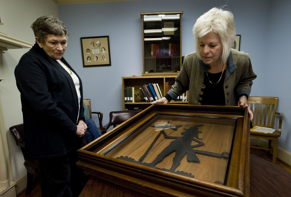 """Elizabeth Stevenson, left, president of the Woodstock Library, looks on as Barbara Adamson, president of the Shenandoah County Historical Society, gets a close-up   look at the """"Swiss Guard"""" that was once on top of the old courthouse from the late 1700s to the early 1800s. Rich Cooley/Daily"""