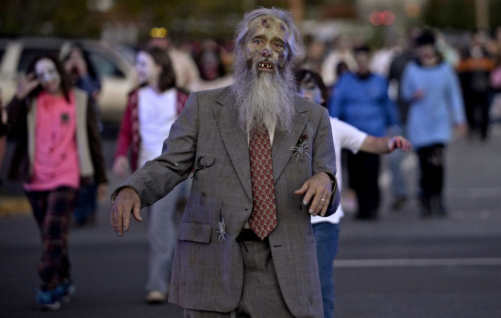 Rick Dutrow, of Stephens City, leads several dozen zombies across Commerce Avenue in Front Royal  during last year's Zombie Walk.  This year's Zombie Walk starts at Bing Crosby Stadium at 6 p.m. Saturday and will proceed down Warren and Chester streets toward the town commons.   Rich Cooley/Daily file