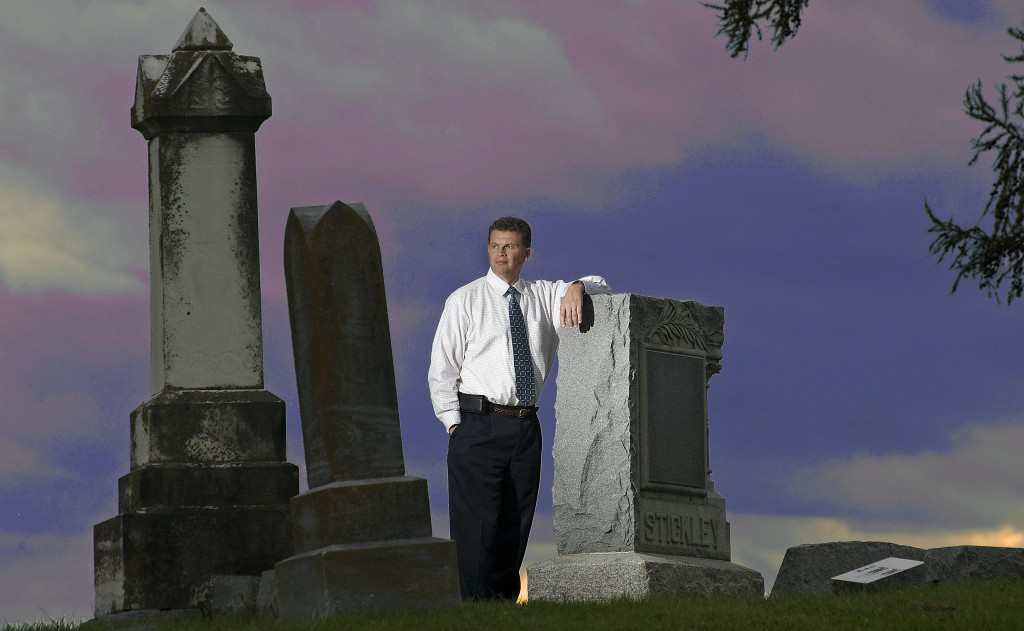 Strasburg Mayor Tim Taylor stands in Riverview Cemetery off South Holliday Street in town. The town is sponsoring a graveyard tours on Saturday. Rich Cooley/Daily file
