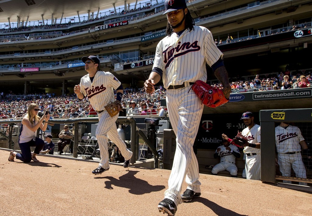 Brea Hinegardner, at left, photographs Minnesota Twins starting pitcher Ervin Santana, at right, and second baseman Brian Dozier, as the pair take the field this past July. Hinegardner, a 2010 Central High School graduate, is the digital communications specialist for the MInnesota team. Photo by Minnesota Twins team photographer Brace Hemmelgarn.