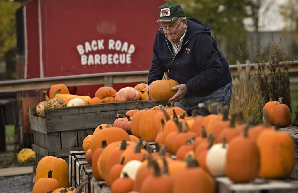 Jim Douglas, 84, of Winchester, adds a pumpkin to this display outside Woodbine Farm Market in Lebanon Church on Thursday.  Read about Halloween trick-or-treat hours and activities on B9. Rich Cooley/Daily