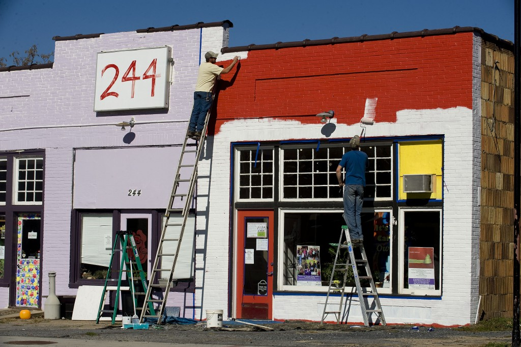 Damon Padgett, left,  and Kendall May, owners of PH Landscapes in Front Royal, apply primer to this building on West King Street in Strasburg recently. The building will be painted purple. Rich Cooley/Daily