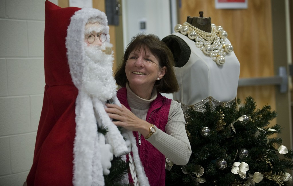 Regina O'Brien, executive director of Winchester Youth Development Center, tidies a pair of Christmas trees      decorated for sale as part of their holiday fundraiser.    Rich Cooley/Daily