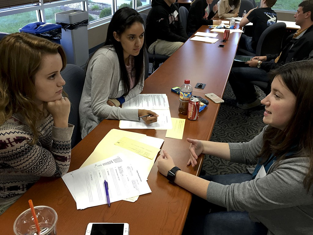 Liz Lewis, right, American Woodmark CFO assistant, discusses FBLA competitive events with Sherando seniors Autumn Gordan and Danielle Mudd. Rachel Mahoney/Daily