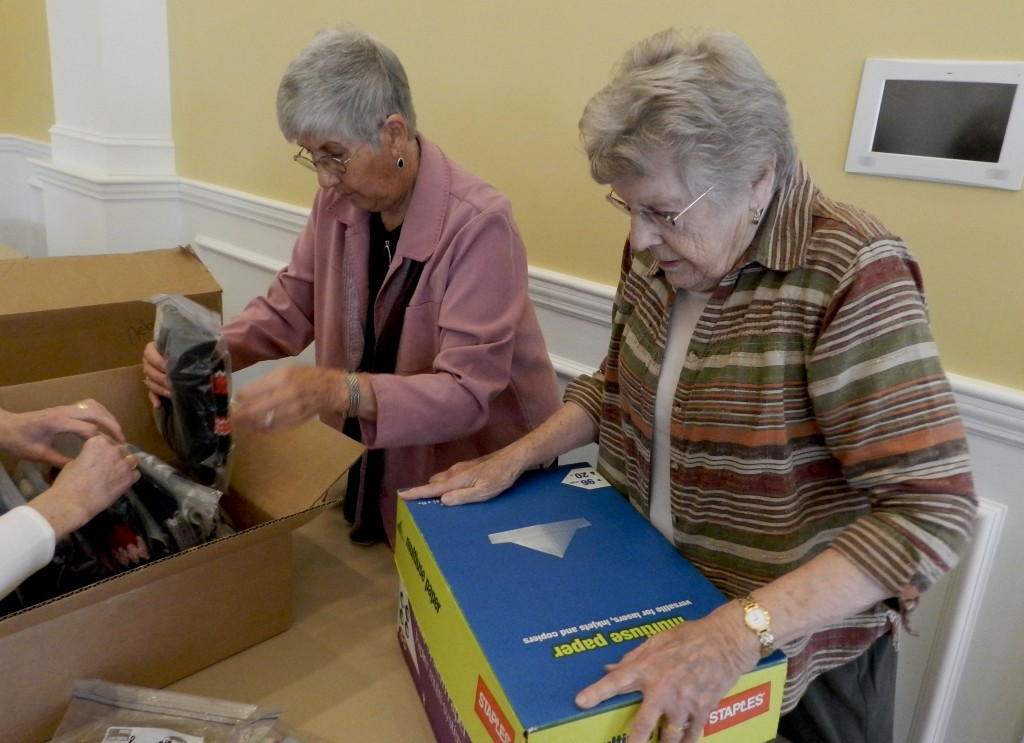 Jan White and Ann Bohnet, both members of The Village at Orchard Ridge's Flying Fingers knitting group, package up hats and scarves for needy children in Winchester. Rachel Mahoney/Daily