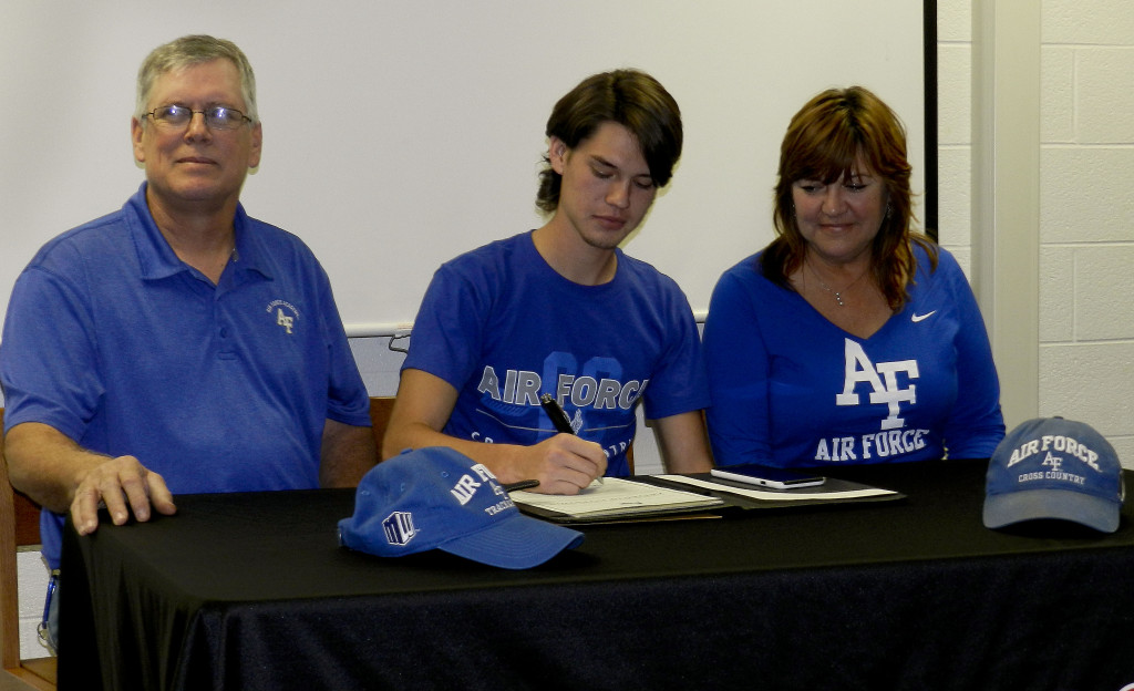 Sherando senior Trevor Whiteside, center, signs with Air Force Academy for coross country and track on Tuesday at the Sherando library. His father, Guy, is on the left, and his mother, Terri, on the right. Tommy Keeler Jr./Daily