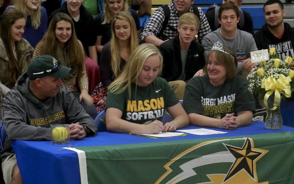 Central High School senior Bekah Ansbro signs a national letter of intent to play softball at George Mason University during a ceremony on Wednesday morning in Woodstock. Ansbro is accompanied by her father  Mike, left, and mother Margaret.   Brad Fauber/Daily