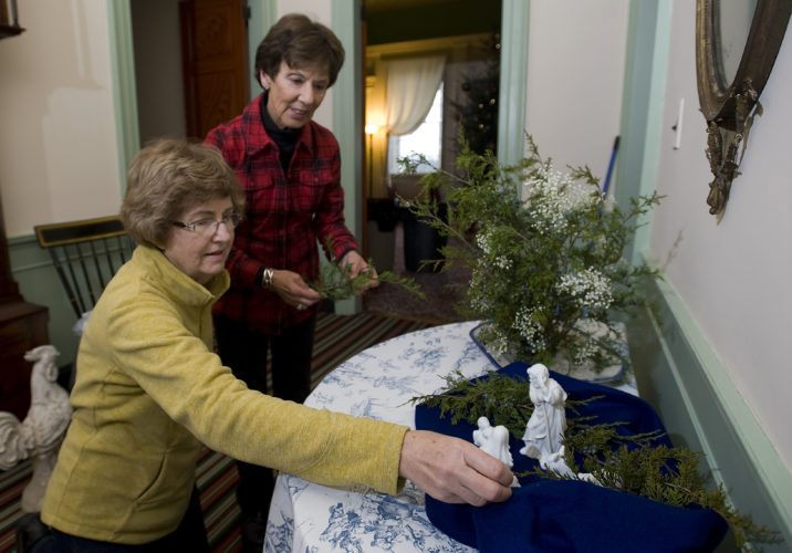 """Sue Cobb, left, and Jeane Eastham, right, both members of Valley Garden Club in Front Royal, decorate the foyer inside Belle Grove mansion in Middletown on Wednesday. Area garden clubs decorated rooms in the mansion,  with each creating decorations for the """"Christmas Around the World"""" theme. Rich Cooley/Daily"""