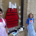 Youssef Ouakil, left, an A.S. Rhodes Elementary School fifth grader, and Sebastian Ward, a Leslie Fox Keyser Elementary School fifth grader, stand beside their holiday window painting in front of the Front Royal Town Hall building on Main Street. Courtesy photo by Warren County Public Schools elementary art teacher Laura Walthall