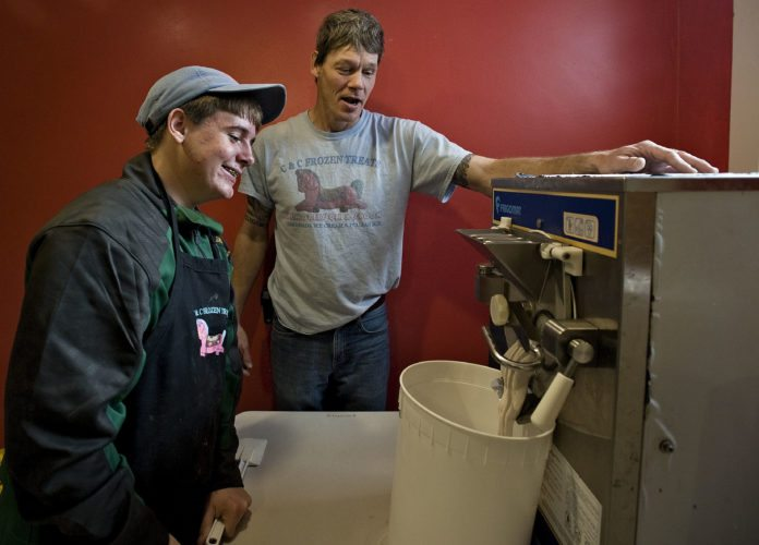 Shenandoah Valley Christian Academy student Luke Shollenberger, 15, of Front Royal, watches as his chocolate pomegranate ice cream recipe flows out of the ice cream machine as C & C Frozen Treats owner William Huck looks on. Rich Cooley/Daily