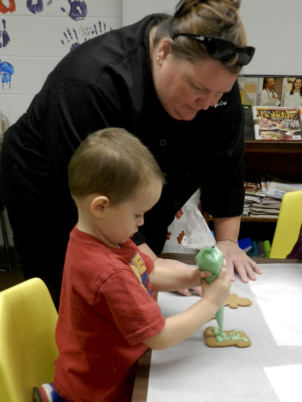 Triplett Tech chef Paje Cross shows preschooler Blake Rice, 3, of Woodstock, how to decorate a gingerbread cookie. Kaley Toy/Daily