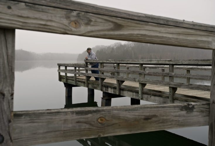Terry Henry, of Summit Point, W.Va., stands along the fishing pier in the afternoon fog over Lake Frederick near Front Royal on Friday afternoon.  Rich Cooley/Daily