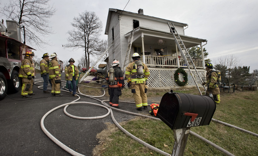 Firefighters stand outside a home at 318 Newman St., in Strasburg where fire heavily damaged the second floor on Tuesday. Rich Cooley/Daily