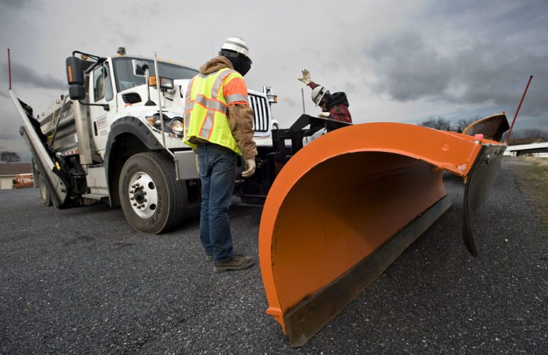 Darrin Lucas, left, and Terry Wetzel, both Virginia Department of Transportation  operators, mount the plow on the department's new wing plow truck at the Stephens City transportation department Thursday.   Rich Cooley/Daily