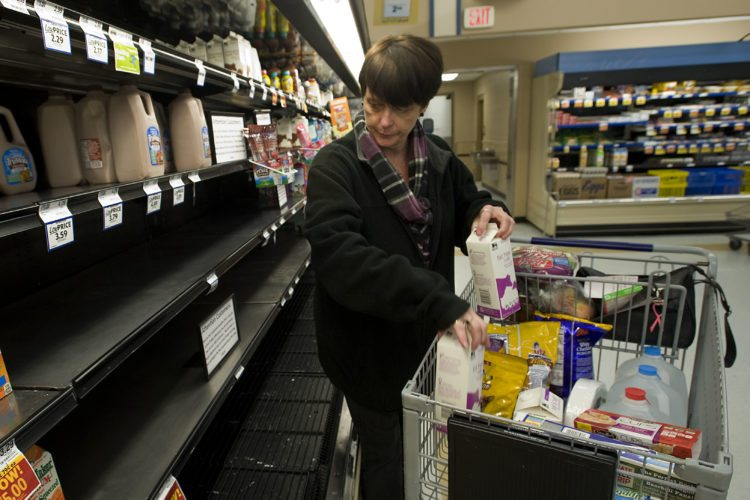 Sue Shipp, of Strasburg, settles for a pair of quart containers of milk as shelf supplies ran out of gallon containers Thursday afternoon at Food Lion in Strasburg.  Rich Cooley/Daily