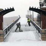 Kenny Hamblin, left, and Andrew Watts, with the Roanoke Parks and Recreation Department, shovel snow on the Martin Luther King bridge on First Street and Salem Avenue as snow falls Friday morning in Roanoke.  Stephanie Klein-Davis/The Roanoke Times via AP