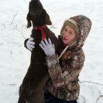 Rachel Tusing hugs her plot hound while it was treeing a squirrel during the storm. Photo courtesy of Lisa Tusing