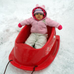 Adalyn George, 8 months, of Woodstock, takes a ride on a bright red sled. Photo courtesy of Sara George