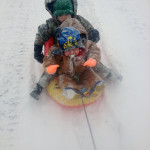 Matthew Kingree Jr., 2, and Maison Kingree, 1, both of Toms Brook, enjoy a sled ride on Friday. Courtesy photo