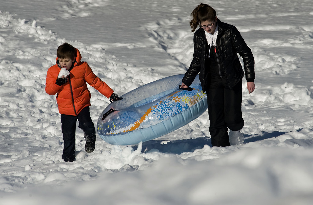 Ryker Fenton, 8, left, and his neighbor Heather Lalumondiere, 14, both of Front Royal, walk up a hill outside Warren County Middle School on Wednesday afternoon after a tubing ride. Warren and Shenandoah County students had Wednesday off and will get another day off today as area schools remain closed following last weekend's snow. Rich Cooley/Daily